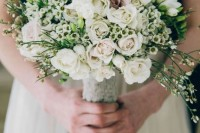 a neutral wedding bouquet done of white and blush blooms and much greenery looks very wild and perfect for a summer wedding