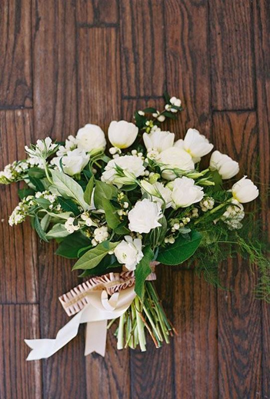 a white wedding bouquet of smaller and larger blooms and much greneery for a textural touch