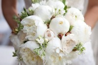 a white peony wedding bouquet with smaller blooms and greenery shaped as a ball