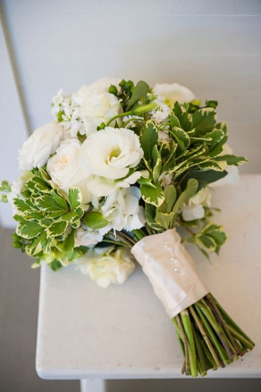 white blooms and catchy greenery wedding bouquet with a shiny wrap on buttons for a rustic look