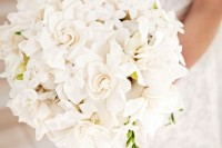 a heavenly white bloom wedding bouquet of various types of flowers shaped as a ball for a romantic touch