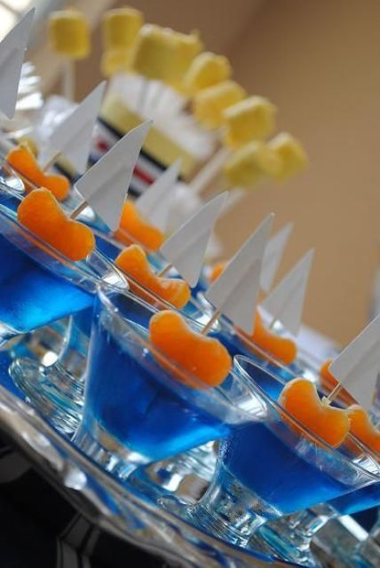 blue jello shots with tangerin and sail toppers imitate boats and are perfect for a nautical bridal shower