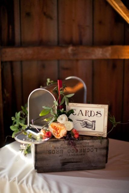 a rough wooden box with a frame and a mailbox where the guests will leave their cards for the couple