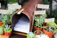 a stylish metal mailbox with letters from your guests inside, place potted succulents that are favors around
