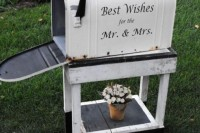 a large vintage mailbox on a matching white wooden stand to gather the wishes to the couple