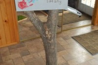 a neutral mailbox decorated with colorful palms and names and placed on a tree stump for a woodland wedding