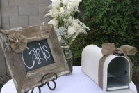 a rustic setting with a white mailbox decorated with burlap, a chalkboard sign in a wooden frame and with burlap flowers