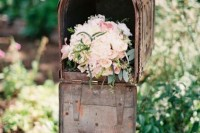 a rust metal mailbox filled with pastel blooms as a pretty and simple wedding decoration
