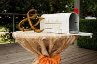 a mini table with a mailbox decorated with monograms and ampersand to leave wishes to the couple