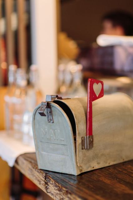 a small farmhouse inspired mailbox, which is whitewashed and with a little heart mark for a rustic wedding