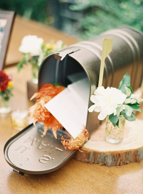 a simple metal mailbox with bright blooms and wishes from the guests to the couple
