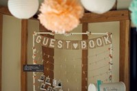 a guest book styled as a frame with clothespins and a mailbox next to it to leave wishes or to take pics from it