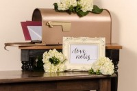 a chic copper mailbox with fresh hydrangeas and greenery on it plus a frame with your names for leaving wishes