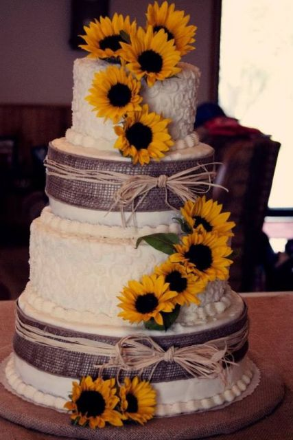 a rustic wedding cake decorated with burlap, yarn and sunflowers for a stylish and simple look