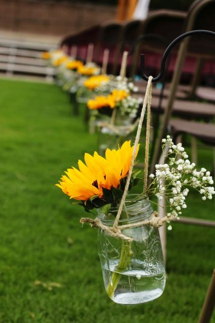 decorate your wedding aisle with baby's breath, sunflowers in a jar for a slight rustic touch
