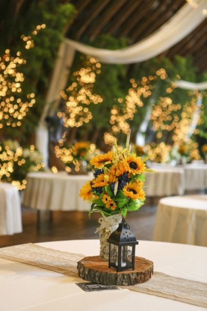 a rustic wedding centerpiece of a wooden slice, sunflowers and greenery and a candle lantern
