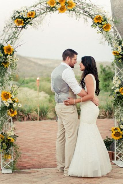 a rustic wedding arch with sunflowers, white blooms and greenery for a summer or fall wedding
