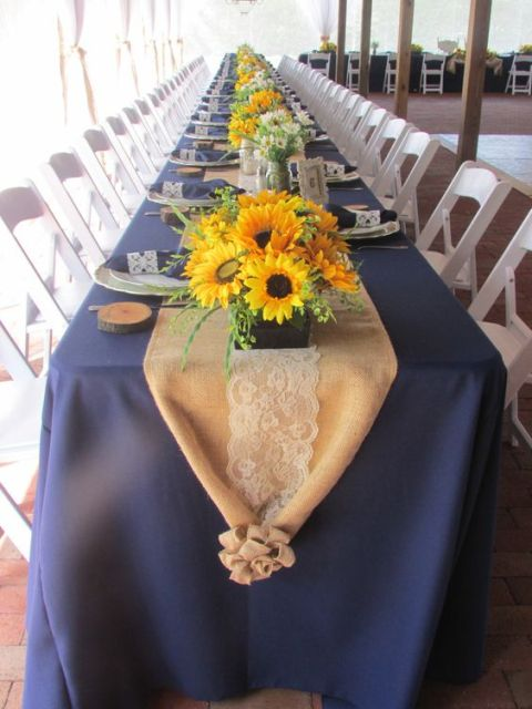 bright sunflower wedding centerpieces with some greenery and a burlap runner for a cozy rustic look