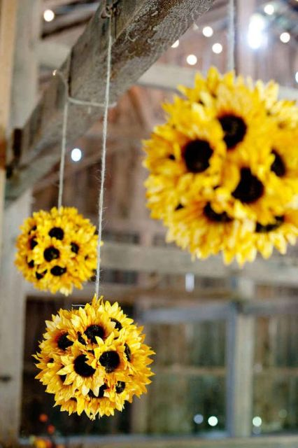 sunflower pompoms hanging over the reception or your wedding arch for a bright rustic look