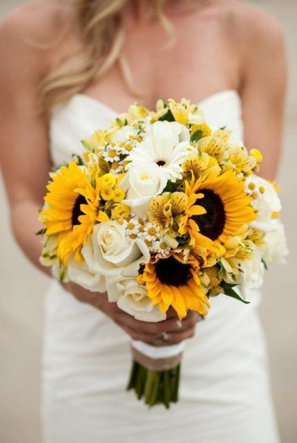 a bright wedding bouquet composed of white and sunny yellow blooms plus some greenery for a rustic bride