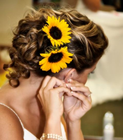 a wavy low updo with some curls down and sunflowers tucked in to embrace the wedding season and theme