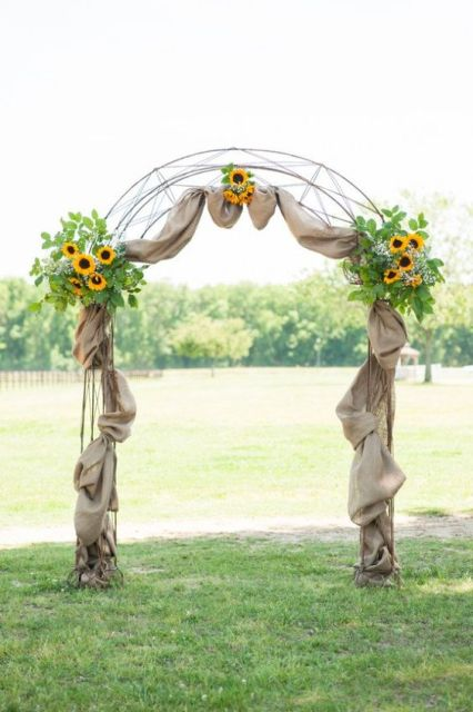 a rustic wedding arch decorated with burlap, greenery and sunflowers looks cool and very cozy