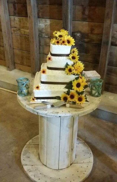 a square wedding cake with dark ribbons and sunflowers for decor is a cool rustic idea for a wedding