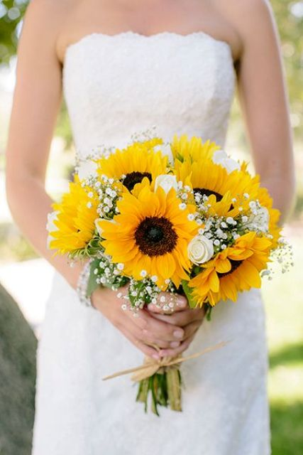 a rustic wedding bouquet of sunflowers, baby's breath and some greenery for a cute look