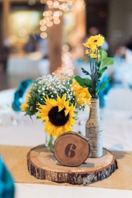 a wood slice, a slice table number, a bottle wrapped with yarn and sunflowers and baby's breath
