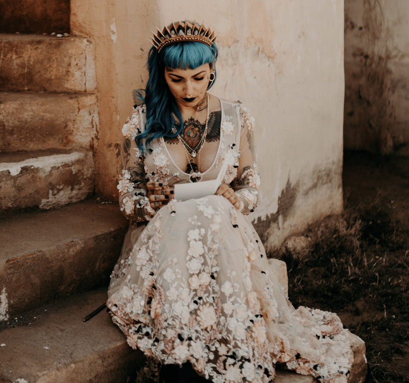 a badass bride wearing a floral applique wedding dress, blue hair with a bold embellished crown and several piercings
