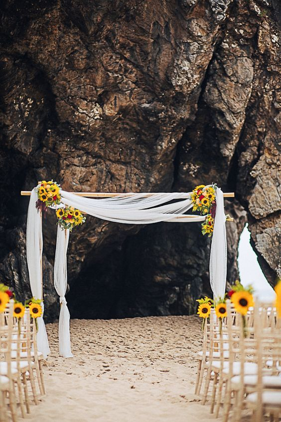 a beach wedding ceremony space done with white fabric and lots of sunflowers for a breezy and cheerful look