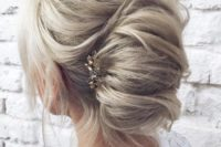 a beautiful French twist updo with a volume on top, some locks down and a rhinestone hairpiece on one side