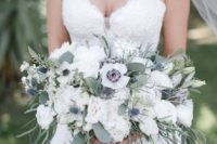 a beautiful and breezy white wedding bouquet of anemones, peonies, thistles and greenery of various kinds