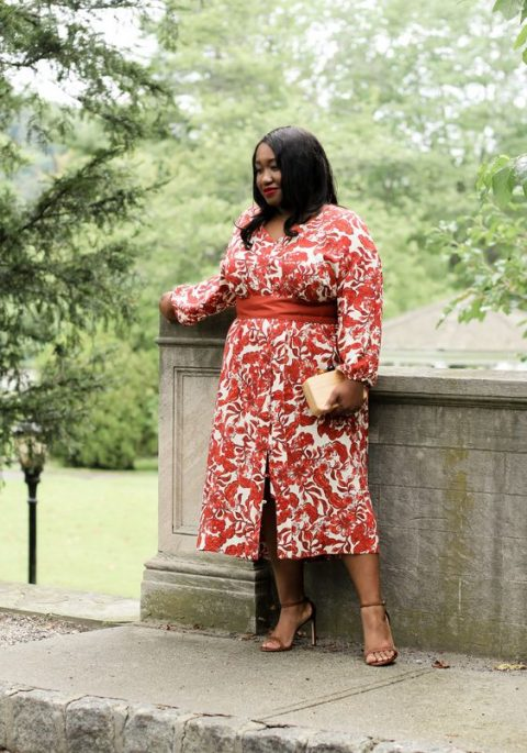 a beautiful botanical print midi dress with long sleeves for a plus size mother of a bride, a front slit, a neutral clutch and tan shoes