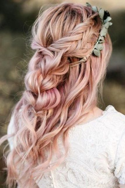 a beautiful pink wedding hairstyle with braids, a braided halo and waves down plus a greenery crown