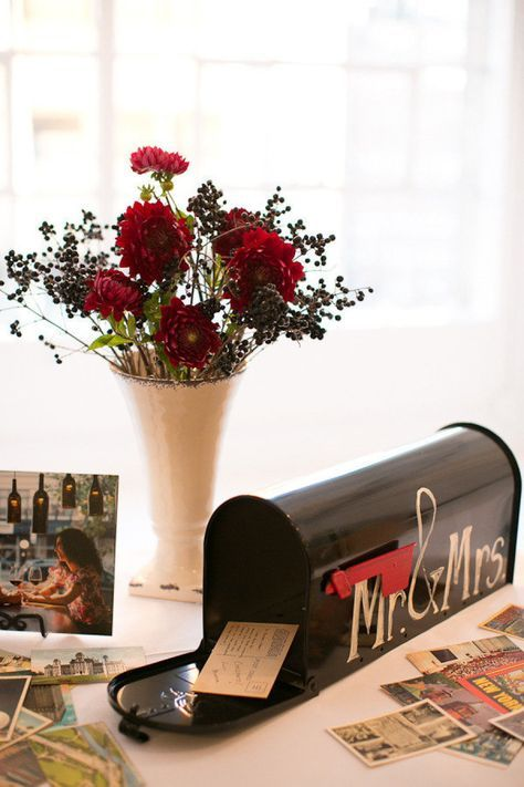 a black mailbox with a red flag and some letters and cards from your guests is a stylish idea, place blooms next to it