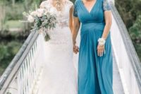 a blue maxi dress with a draped bodice and waist, a deep V-neckline and lace sleeves plus silver shoes