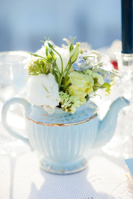 a blue teapot with bright and neutral blooms as a simple rustic or vintage wedding centerpiece