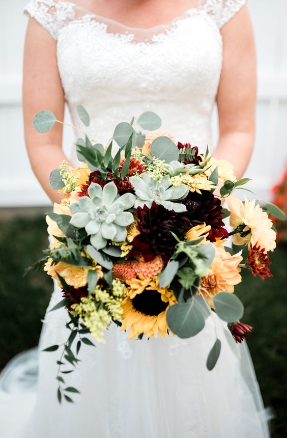a bold fall wedding bouquet with pale succulents, eucalyptus, peachy and yellow blooms and sunflowers