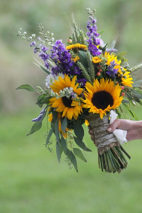 a bold wedding bouquet made of sunflowers, purple and white blooms and much greenery and wheat