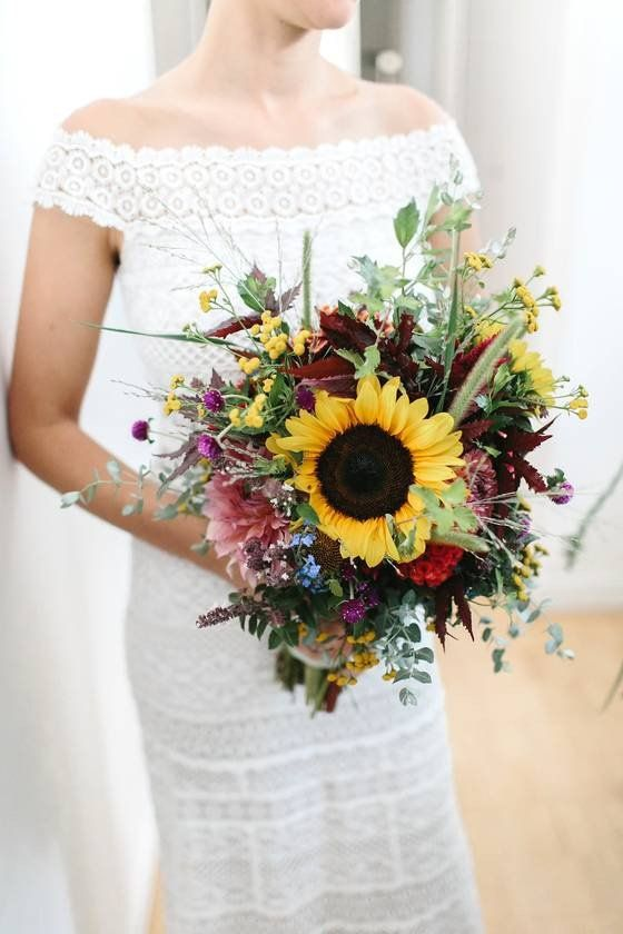 a bright fall wedding bouquet of pink, red, burgundy blooms, sunflowers and various kinds of greenery