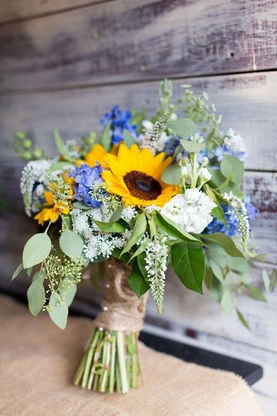 a bright summer wedding bouquet of blue and white blooms, sunflowers and textural greenery