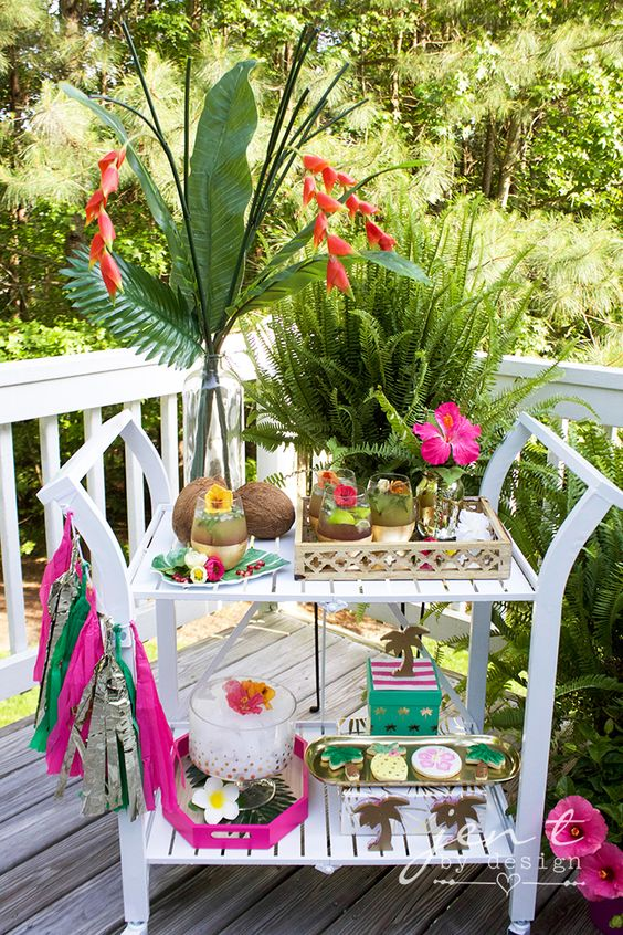 a bright tropical bridal shower cart with coconuts, tropical greenery, colorful tassels and bold blooms