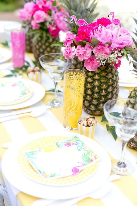 a bright tropical bridal shower table setting with pineapples with bright florals and pink flamingos, yellow glasses and plates and printed napkins