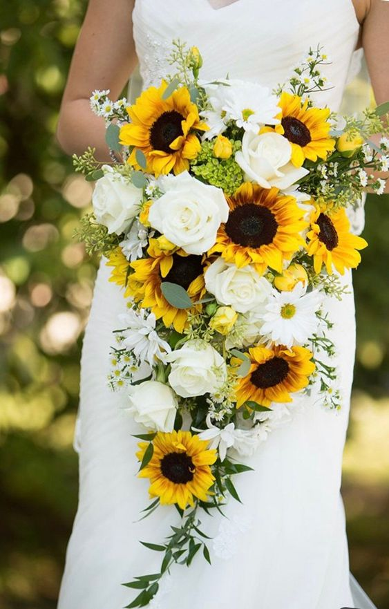 a cascading wedding bouquet of sunflowers, white blooms and some greenery for a summer bride