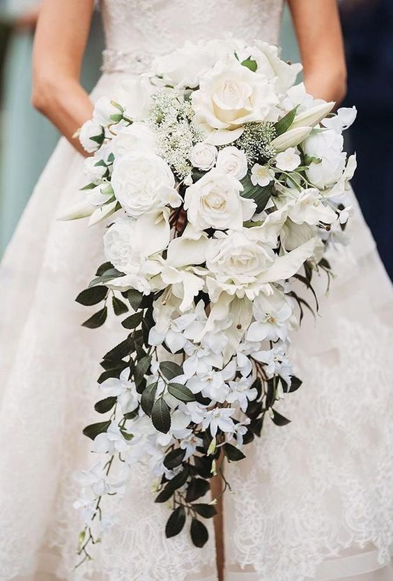 a cascading wedding bouquet with peonies, small and large roses and foliage looks refined and luxurious