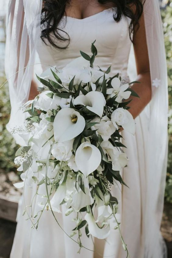 a cascading wedding bouquet with white blooms and callas, with greenery and herbs for a modern tropical bride