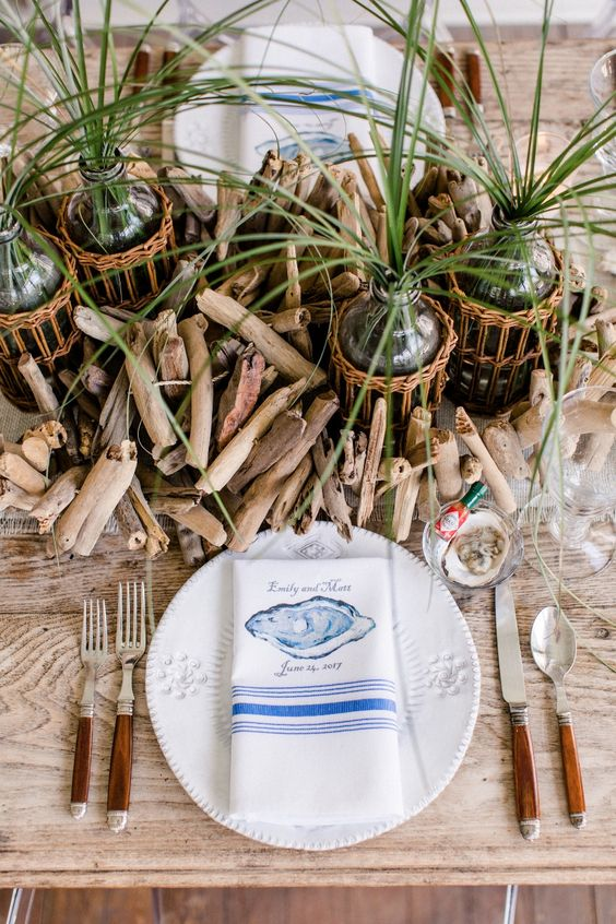 a catchy nautical bridal shower tablescape done with driftwood, grasses, printed blue napkins and shells