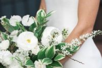 a catchy white wedding bouquet of peonies and roses, some blooms on branches and greenery and leaves