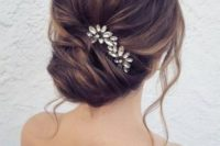 a chic French twist updo with a volume on top and locks down with a rhinestone hairpiece